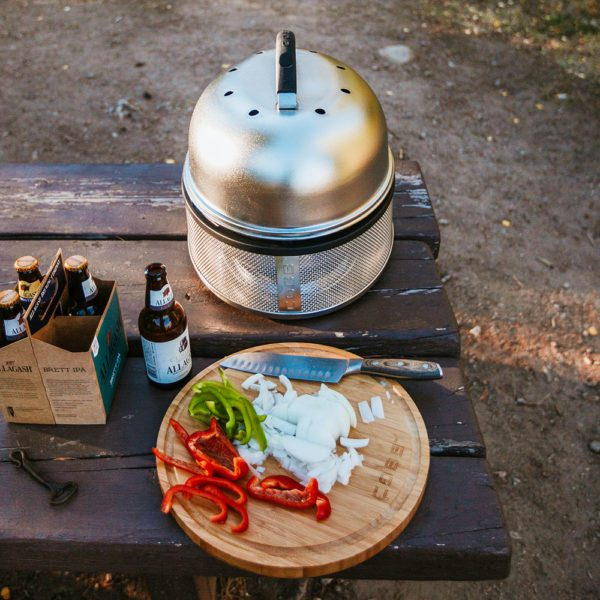 COBB Supreme on outdoor picnic table next to cutting board with veggies and beer